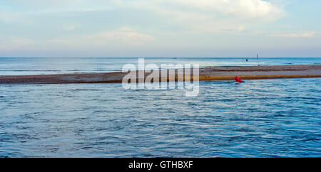 Fast current at the entrance to Christchurch Harbour, a narrow entrance with a sand bar - Stock Photo