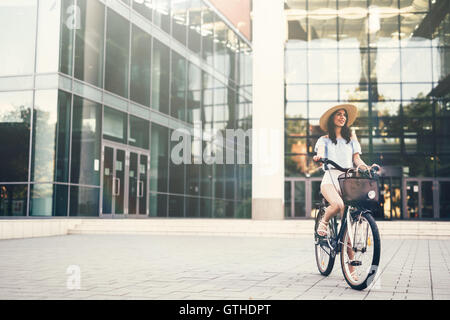 Beautiful woman using bike instead of car - Stock Photo