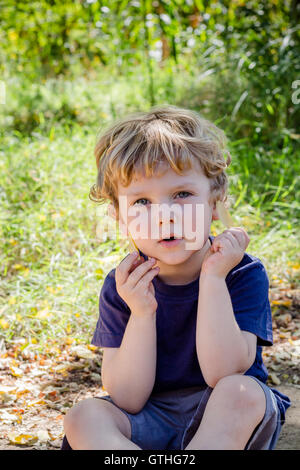 Little blonde boy sitting in long grass looking at camera holding leaves - Stock Photo