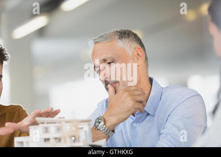 Architects discussing model in meeting - Stock Photo