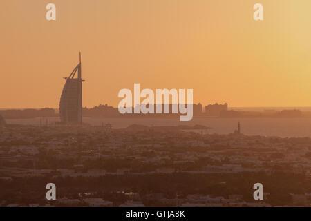 Burj Al Arab the luxury 7 stars hotel and jumeirah beach in panoramic orange silhouette sunset - Stock Photo