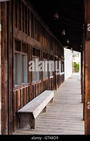 rustic wooden sidewalk with old bench in Winthrop, Washington state, USA - Stock Photo