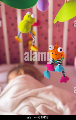 Baby bed with mobile toy above it; baby sleeping - Stock Photo