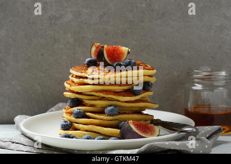 Stack of golden pancakes with fresh fruits, food close-up - Stock Photo