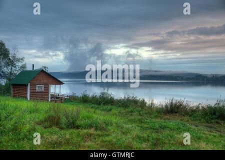 Vintage Russian smoke sauna log cabin on a river shore. - Stock Photo