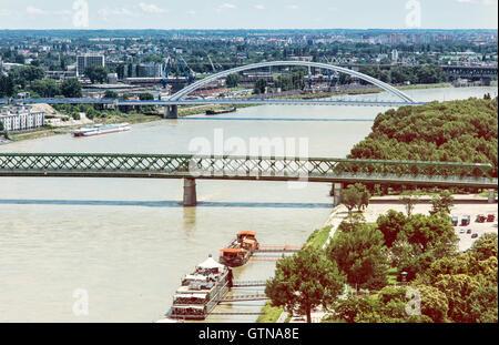 Bridges over the Danube river in Bratislava city, Slovak republic. Old bridge and Apollo bridge. Ship transportation. - Stock Photo