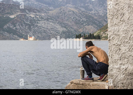 Kotor Bay, Montenegro - Skinny man crouched down on the seashore observes the islet Our Lady of the Rocks (Gospa - Stock Photo