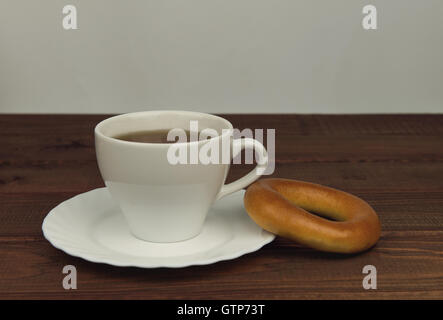 On a wooden table cup of tea and fresh-faced bagel biscuit - small DoF focus put only to pier - Stock Photo