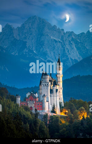 Beautiful view of world-famous Neuschwanstein Castle at night with moon and illumination, Germany, European landmark - Stock Photo