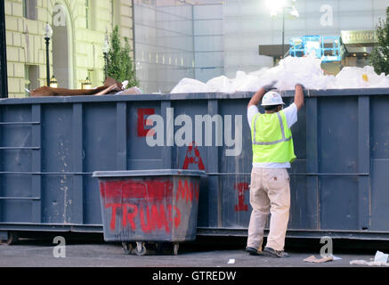 Washington, DC, USA. 09th Sep, 2016. A construction worker throws garbage into a dumpster outside the new hotel - Stock Photo