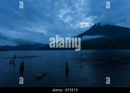 A calm and serene scene of the San Pedro Volcano from Santiago Atitlan at dusk. - Stock Photo