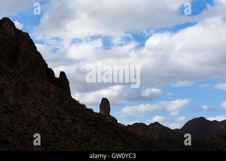 Silhouetted mountains and cactus silhouetted against a partly cloudy sky. Gila River Canyons, Arizona - Stock Photo