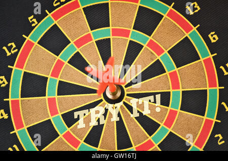 Text Try It written on the circular target with a plastic feather in the center - Stock Photo