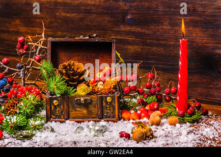 Thanksgiving holiday background with opened chest treasure, apple, nuts, cones, berries, fir tree, candle and snow, - Stock Photo