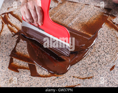 Tempering melted chocolate on table - Stock Photo