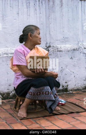Lao matron ready to give alms to Buddhist monks, Wat Sene temple, Luang Prabang, Laos - Stock Photo
