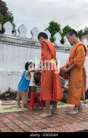Two Buddhist monks receiving rice alms from a small boy, Wat Saen, Luang Prabang, Laos - Stock Photo