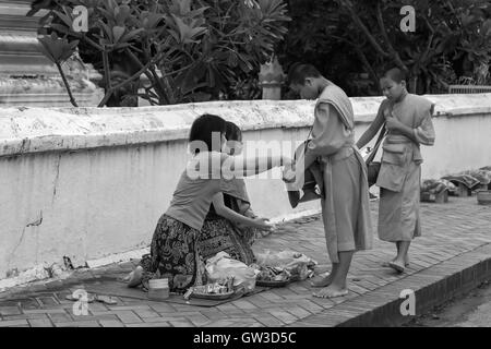 Pre-dawn, young Buddhist monks receive alms from local women, Wat Saen temple, Luang Prabang, Laos - Stock Photo