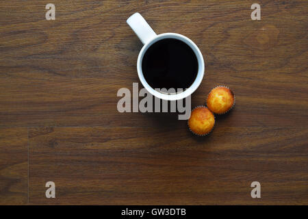 Top view of cup of coffee and muffins on a wooden table. Break from work, lifestyle concept. - Stock Photo