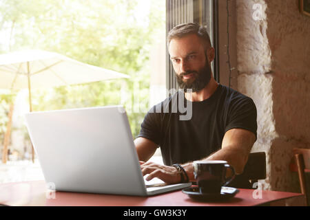 Handsome Bearded Businessman Wearing Black Tshirt Working Laptop Wood Table Urban Cafe.Young Manager Work Notebook - Stock Photo
