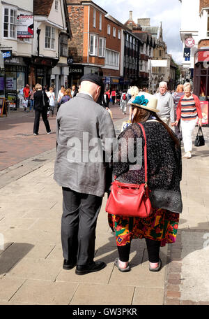 eccentric middleaged couple walking together in the high street of city of canterbury east kent uk september 2016 - Stock Photo
