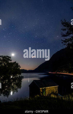 View of Llyn Ogwen Lake at night before sunrise with blu sky, moon and stars. House in the lake and tree. - Stock Photo