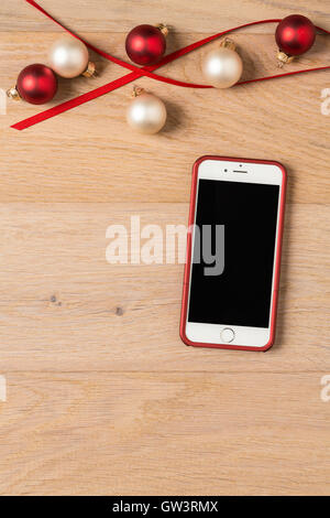 Cell phone iPhone 6 with festive holiday Christmas decorations on rustic wood background - Stock Photo