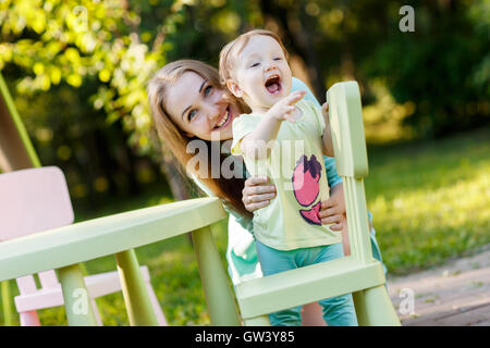 Mother with sitting on children's chair in park - Stock Photo