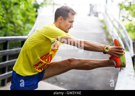 Young men performs stretching before jogging - Stock Photo