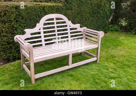 Wooden artisan bench on grassy lawn. - Stock Photo