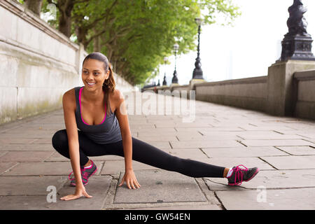 fitness woman stretching her leg muscles before going running - Stock Photo