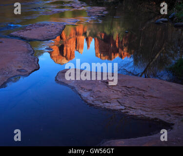 Cathedral Rock at sunset reflected in the still waters of Oak Creek in Sedona, Arizona - Stock Photo