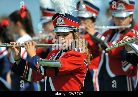 Marching band members playing during a halftime performance at a high school football game. USA. - Stock Photo
