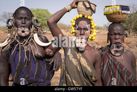 Three Mursi women of the Omo Valley in Ethiopia with lip plates, bone earring, headdresses and ritual body paint, - Stock Photo