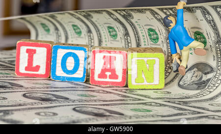 Loan spelled out in blocks with money and figurine - Stock Photo