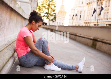 young woman feeling her painful ankle after exercise - Stock Photo