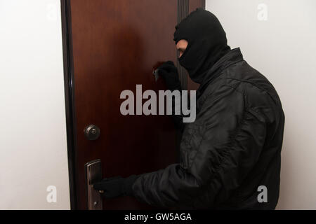 Burglar Breaks Into A Residential Building And Thief In The Mask Covers Peep Hole - Stock Photo