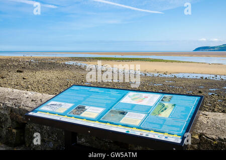 Bilingual information sign about GeoMon Global Geopark overlooking the sands in AONB at Red Wharf Bay Isle of Anglesey - Stock Photo