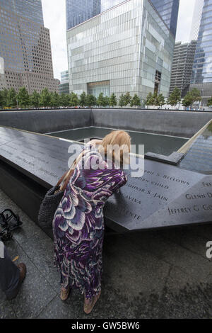 woman takes a photo at the North reflecting pool at the 9/11 Memorial site in Manhattan. - Stock Photo