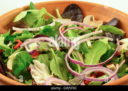 Organic mixed greens, red onion, mushroom and sprouted tofu salad served in wooden bowl, on white background - Stock Photo