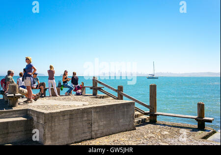 Sausalito, USA - September 23, 2015: Tourists on a pier looking at the bay with the San Francisco skyline in the - Stock Photo