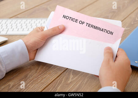 Fired business man reads the notice of job termination - Stock Photo