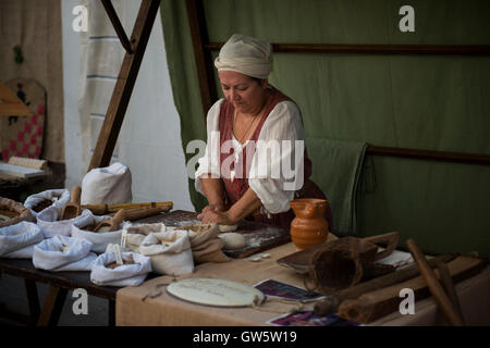 A traditional baker kneading dough at a market stand during the Medieval festival 'Macia' in Spilimbergo, northern - Stock Photo