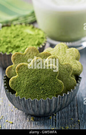 Matcha green tea latte and cookies on a wooden background - Stock Photo