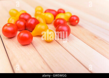 Beautiful mature multicolored tomatoes on wooden boards. - Stock Photo