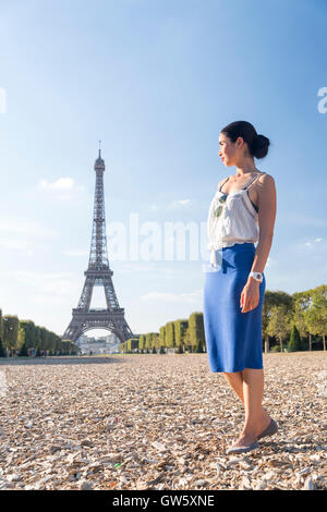 Young woman looks back at the Eiffel Tower, Paris, France - Stock Photo