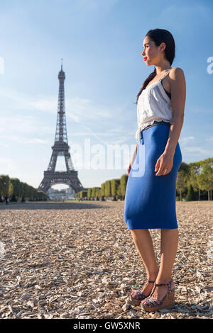 Fashionable young woman looks back at the Eiffel Tower, Paris, France - Stock Photo
