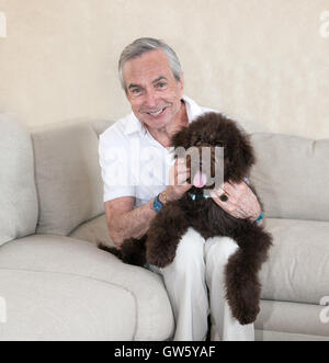 Clean cut slim and grey senior elderly man sits on a beige couch, with his pet companion labradoodle  puppy dog - Stock Photo