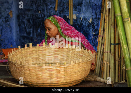 Jodhpur - AUGUST 23: An indian woman in colorful sari braiding a basket at traditional handicraft bazaar in Jodhpur, - Stock Photo