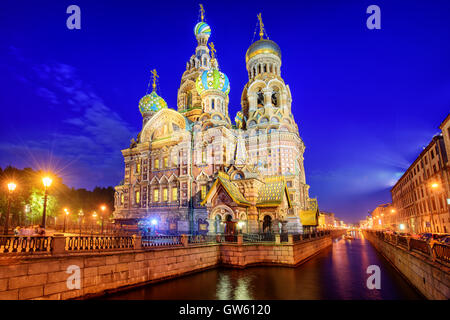 The orthodox Church of the Savior decorated with colorful onion domes on Griboyedov Canal illuminated at evening, - Stock Photo